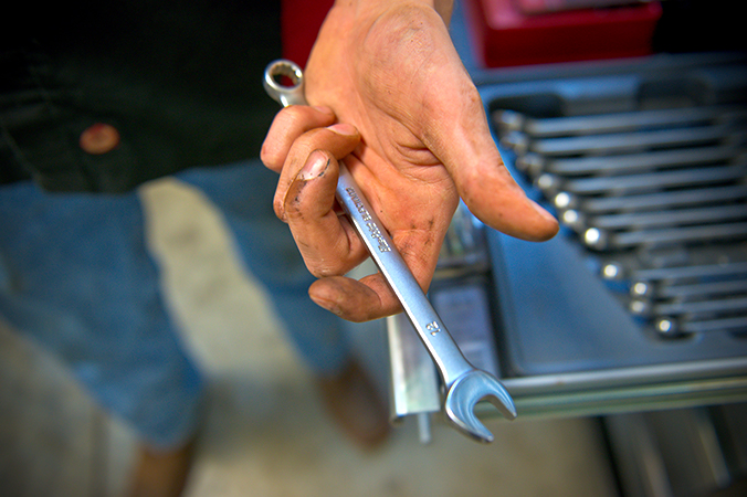 A hand hoding a wrench out to the cammera