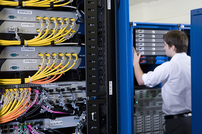 Tech in server room with networking equipment