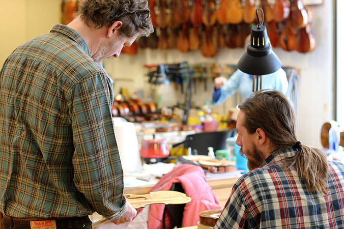 Instructor and student working in a violin shop