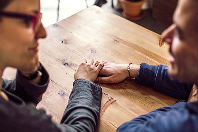 Two people touching hands at a table - photo by Juan Pablo Serrano Arenas from Pexels