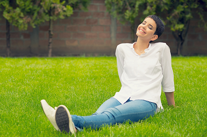 Woman smiling while sitting in the grass